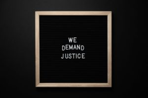 """Blackboard with """"We Want Justice"""" on it"""