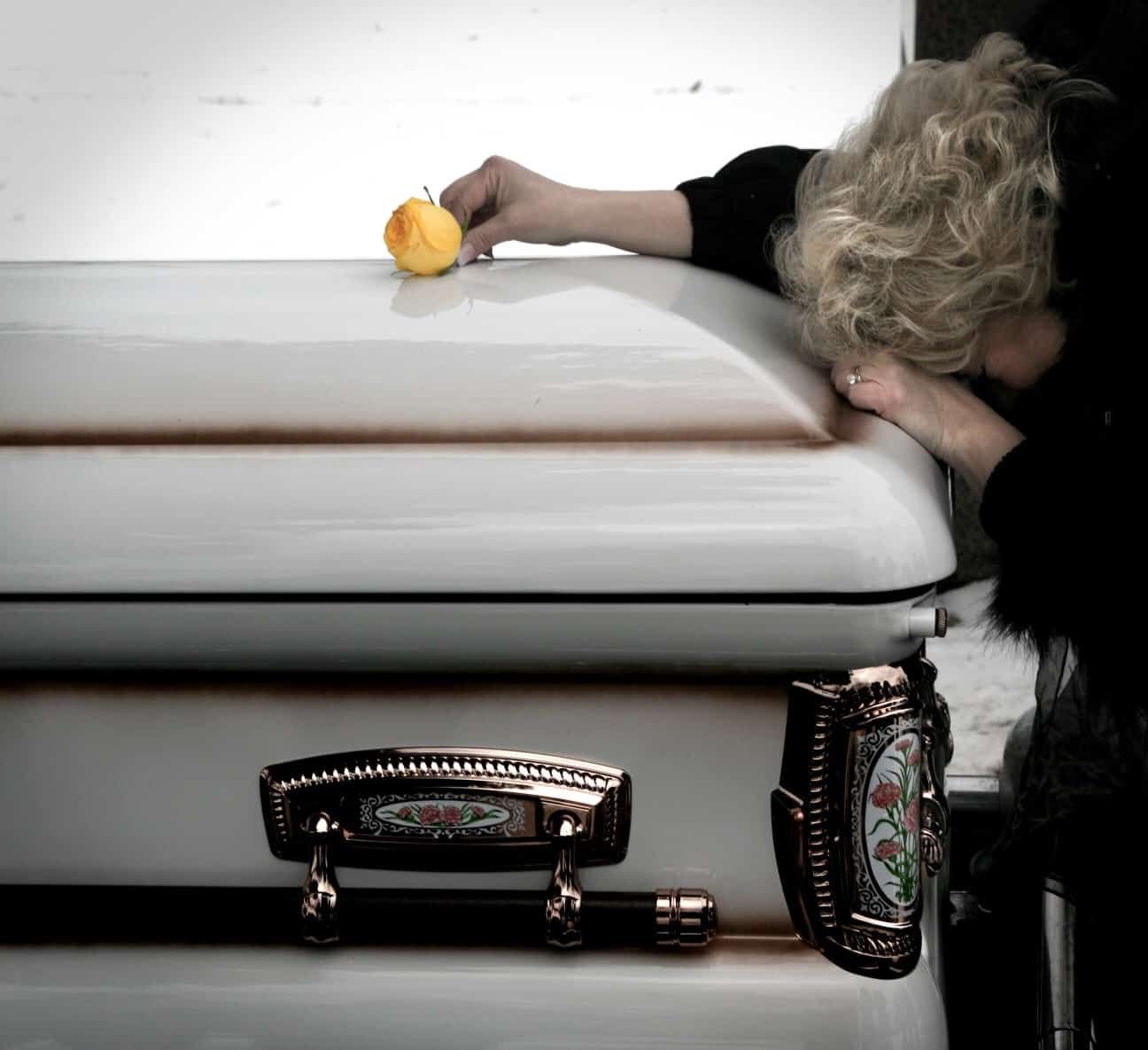 Woman laying over casket with a rose