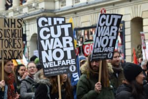 """People carrying signs saying """"Cut War Not Welfare"""" at a protest"""