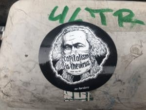 """Sticker saying """"Capitalism is a virus"""""""