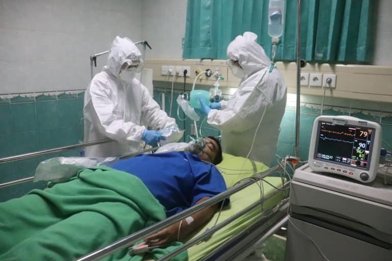Nurses treating patient while wearing PPE
