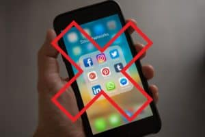 A big red X over a picture of social media displayed on a smartphone