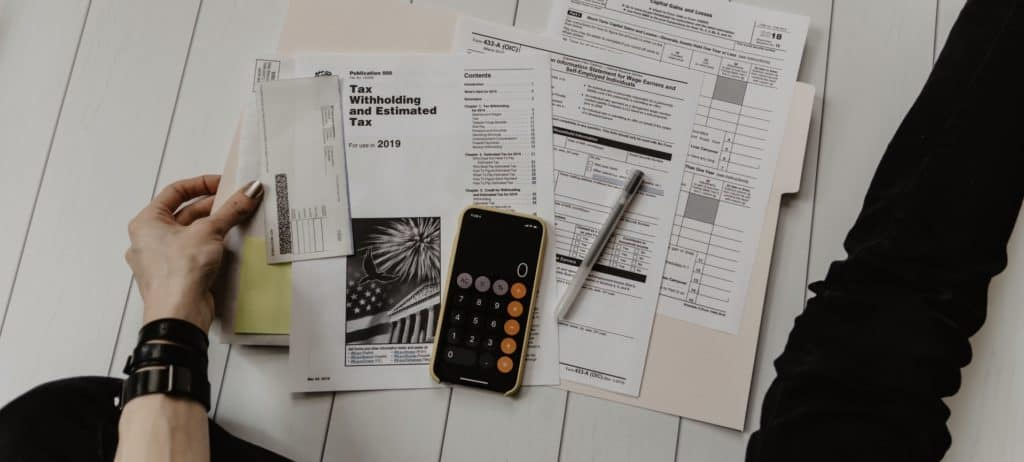Tax forms on a desk with a calculator and pen