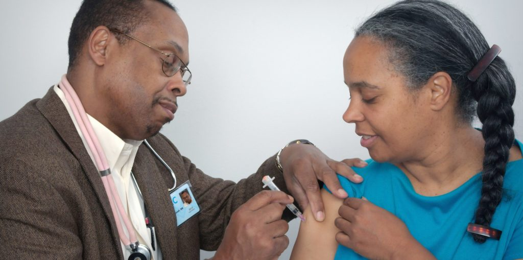 African American woman getting Covid vaccine from African American male doctor