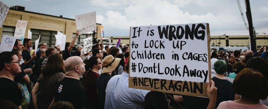 Sign against locking up immigrant kids in cages