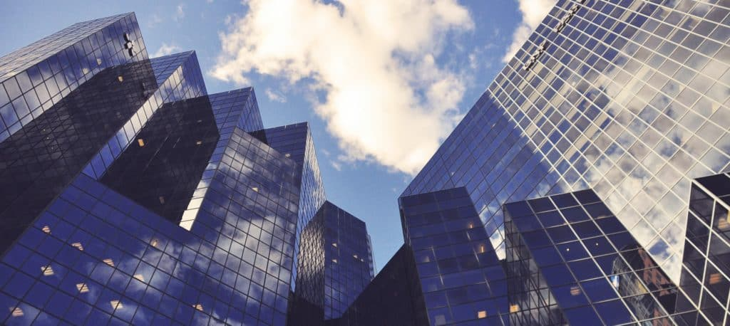 view of tall skyscrapers from below, blue sky, mirrored windows