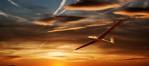Glider flying under sunset clouds