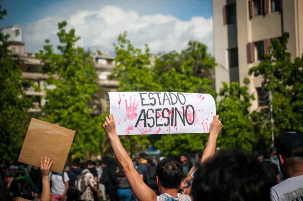 Protester with sign reading Estado Asesino