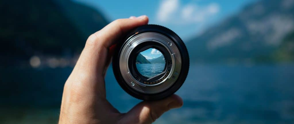landscape viewed through a camera lens held by a person's hand