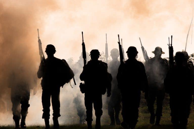 silhouette of soldiers walking through smoke