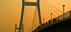 people walking across a suspension bridge at sunset