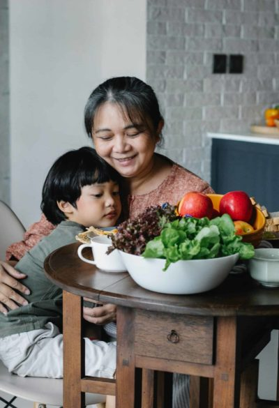 A woman comforting a child on her lap at a kitchen table