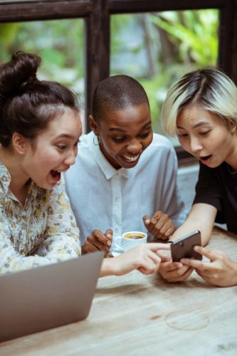 three young women excitedly looking at a phone screen