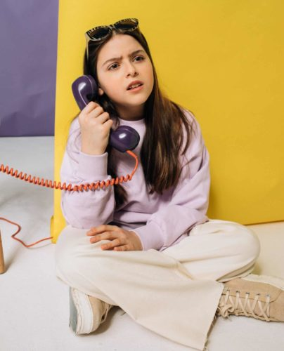 a confused young woman holding an old corded phone receiver to her ear