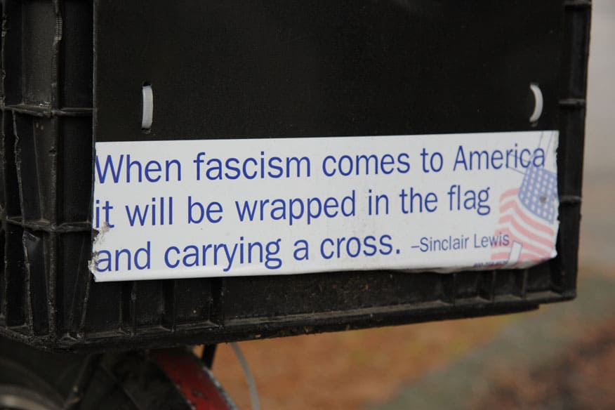 """Closeup of bumper sticker with famous Sinclair Lewis line """"When fascism comes to America it will be wrapped in the flag and carrying a cross"""""""