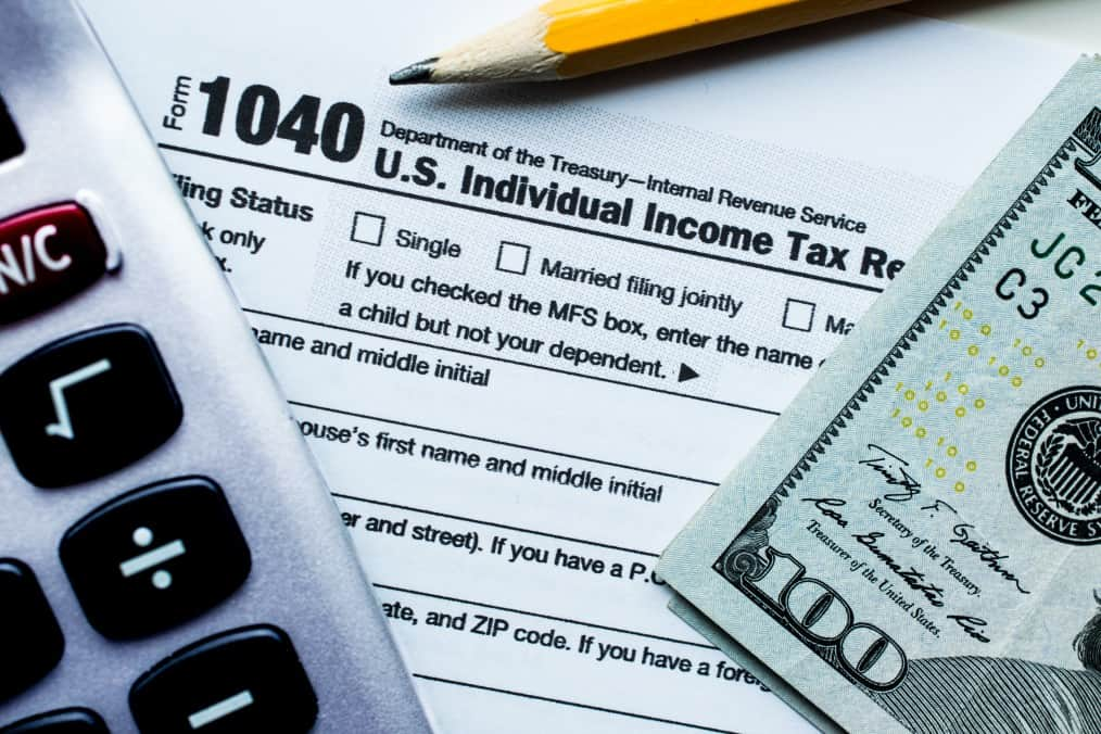 Filing federal income taxes, calculator, and $100 bill