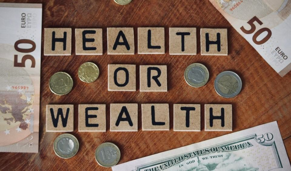 Health or wealth , money , bills and coins , choices , flatlay , wooden blockletters , quote