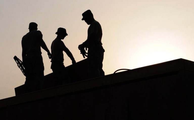Silhouette of workers on a roof