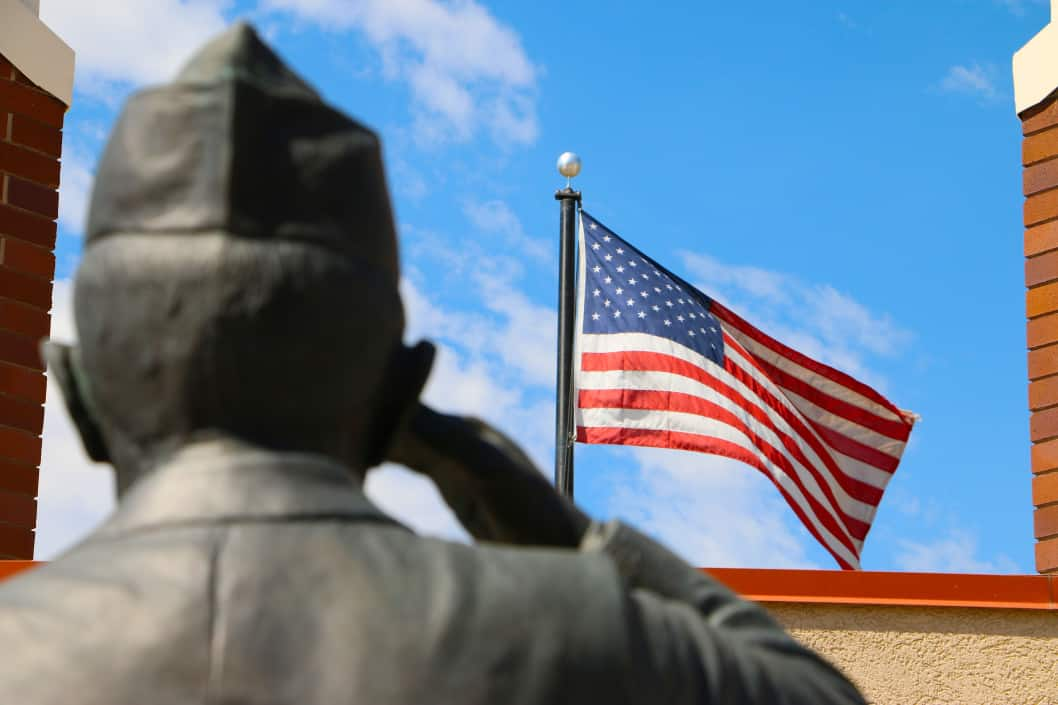 Salute to Veterans: Statue of soldier saluting with American flag flying in the background.