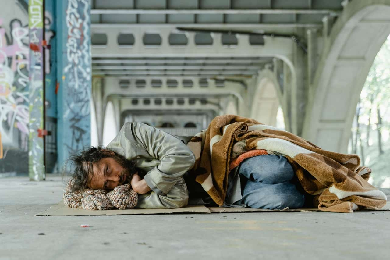 Homeless guy laying down under an overpass