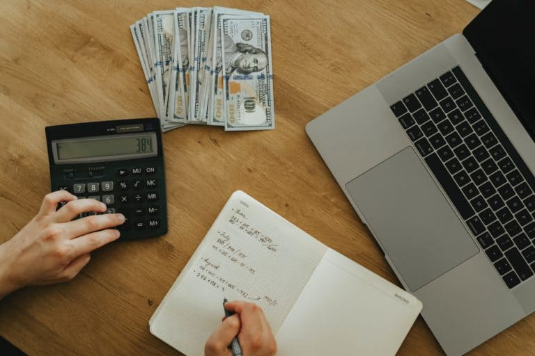 Picture of a person writing in a ledger with a calculator and computer